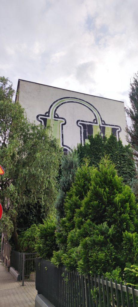Mural częściowo zakryty przez roślinność w okolicach Katowickiego Załęża